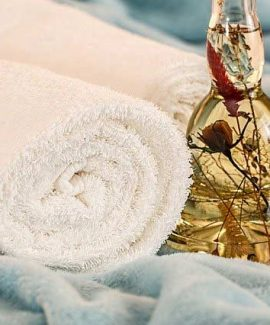 rolled towel and massage oil